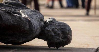 متظاهرون يحطمون تمثالاً لكريستوفر كولومبوس في مدينة بالتيمور الأميركية image